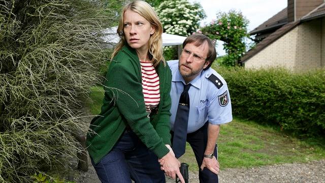 Kommissarin mit gezogener Waffe und Polizist hinter einem Busch.