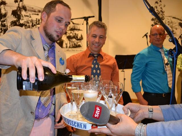 Ein Mann schenkt Champagner aus.