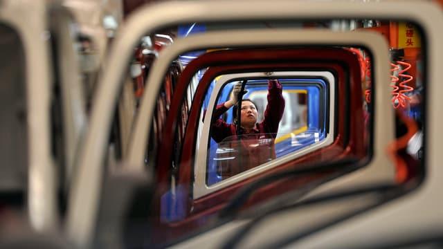 Audio-Produktionsstrasse in China; ein Abeiter montiert ein Teil an einer Autotüre.