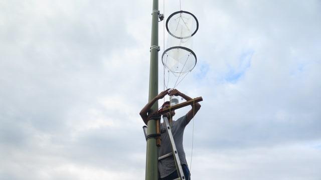 Ein Mann fingert auf einer Leiter an einer Laterne rum.