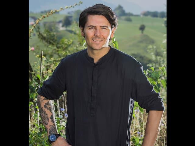 Porträt von Nenad Mlinarevic in einem schwarzen Hemd mit hochgekrempelten Ärmeln.