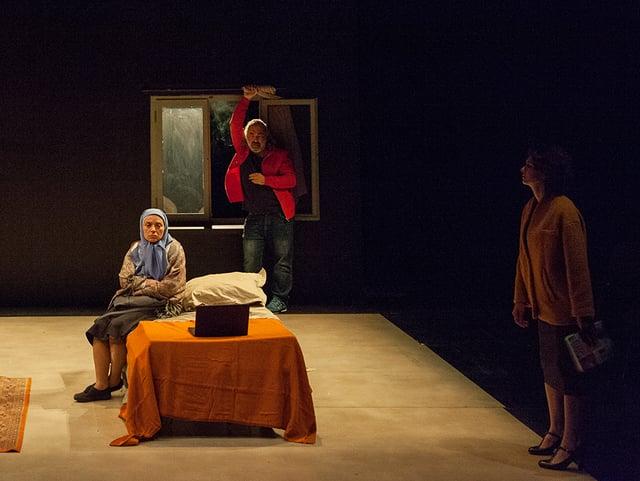 Theaterszene: Eine Frau sitzt auf einem Stuhl, eine Frau auf einem Bett.