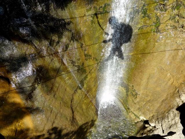 Der Schatten einer Person auf einer Seilbrücke fällt auf den dahinterliegenden Wasserfall.