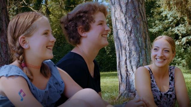 Tamara, Noémi und Anna Zöllig sitzen auf einer Wiese.