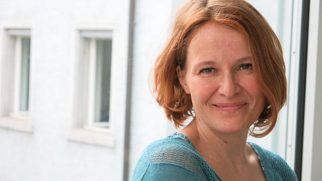 Esther Pauchard steht vor dem Fenster und lächelt in die Kamera.