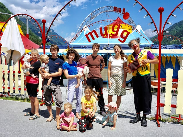Vor dem Eingang zum Areal mit dem Zirkuszelt steht Familie Mugg an einem sonnigen Sommertag.