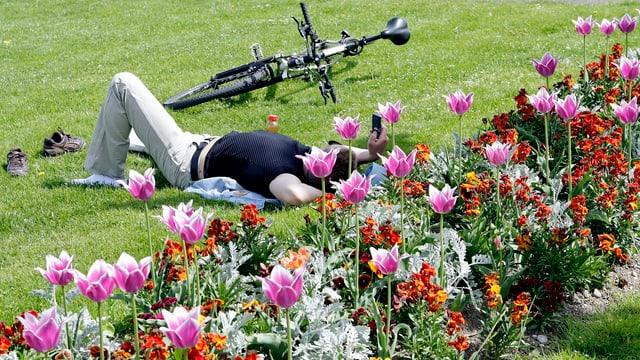 Blumen, Wiese, Velo und liegende Person.