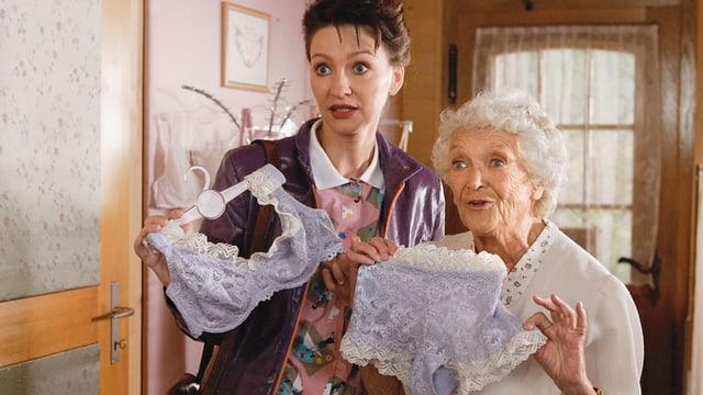 Zwei Frauen präsentieren Spitzenunterwäsche.
