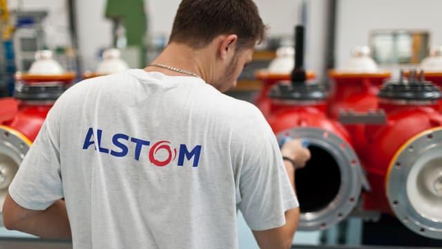Arbeiter mit Alstom-Logo auf T-Shirt arbeitet an Hochspannungsprodukten.