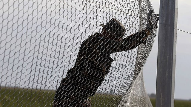 Ein Flüchtling drückt einen Zaun ein.
