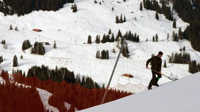 Mann am Schnee schaufeln in Skigebiet