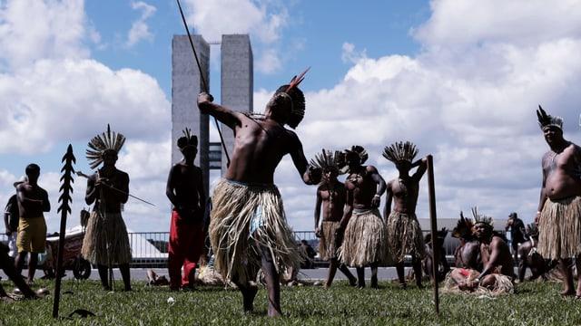 Indigene in traditioneller Tracht vor Hochhäusern.