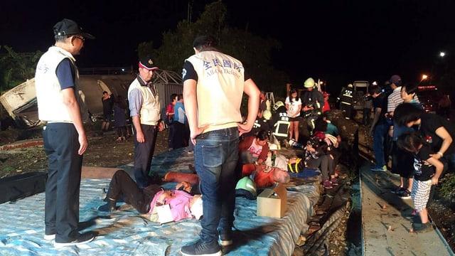 Rettungskräfte stehen um Verletzte. Im Hintergrund der verunglückte Zug.