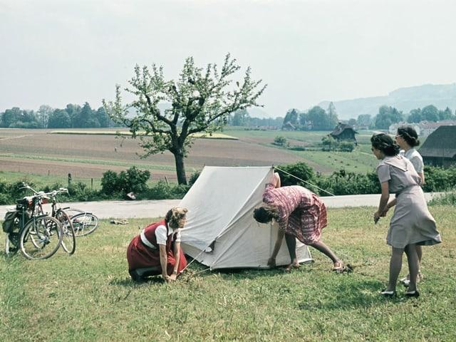 Junge Frauen geniessen im Mai 1944 einen Radausflug in ländlicher Gegend in der Schweiz und zelten auf einer Wiese.