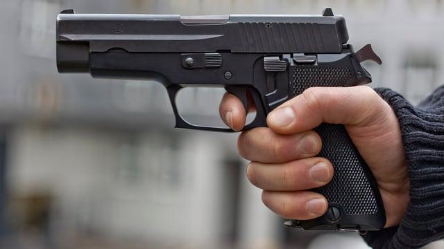 Um cun ina pistola enta maun.