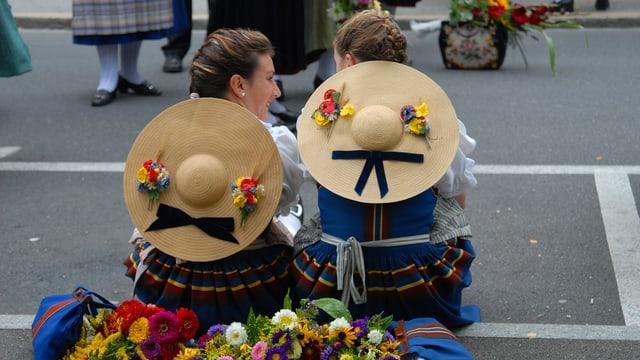 Zwei Trachtenfrauen mit grossen Strohhüten sitzen nebeneinander am Strassenrand.