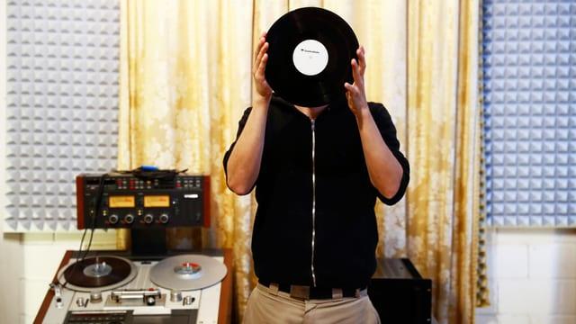 Ein Mann hält eine Vinyl Schallplatte vor sein Gesicht.