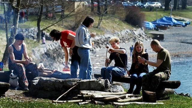 Junge Leute sitzen um eine Feuerstelle und grillieren.