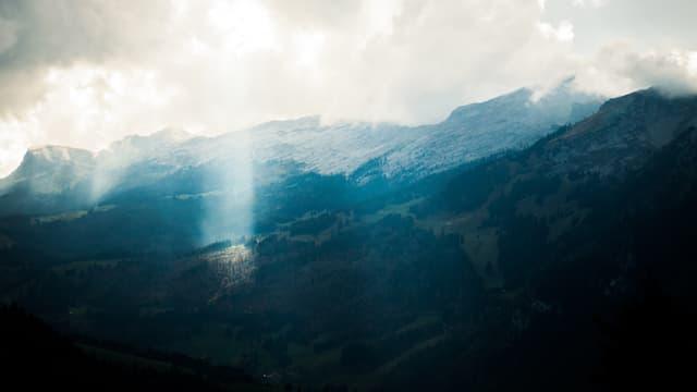 Berge mit Schnee, darüber Wolken, die Sonnen scheint herein.