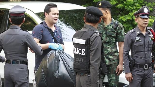 Polizisten tragen Müllsäcke.
