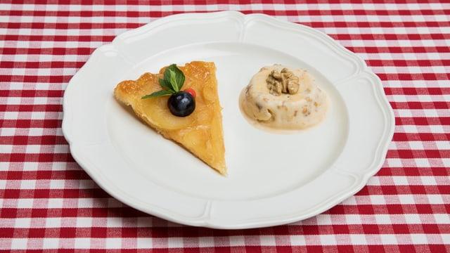 Angerichteter Dessertteller auf rotweiss-karierter Tischdecke.