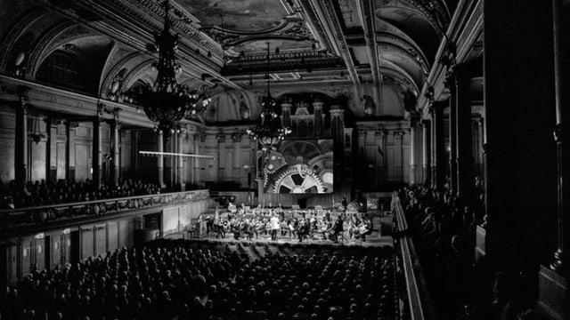 Schwarz-Weiss-Fotografie von einem vollen Konzertsaal.