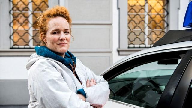 Eine Frau in Schutzanzug vor einem Polizeiwagen.