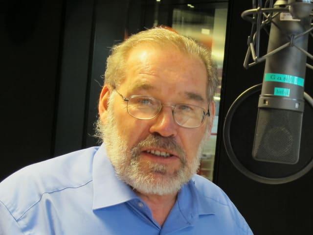 Mann mit Brille und Bart und blauem Hemd neben einem Mikrofon.