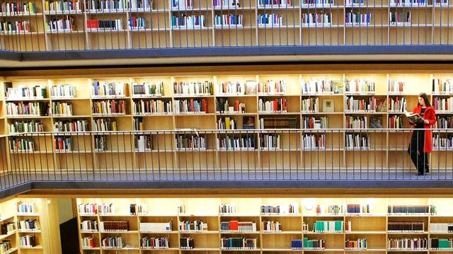 Blick in die Regale verschiedener Stockwerke einer Bibliothek, davor stehend eine lesende Frau.