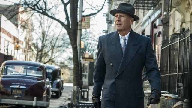 Ein Mann mit grauem Mantel, Hut und schwarzen Lederhandschuhen.