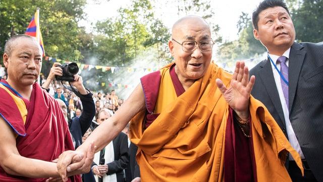 Der Dalai Lama in orangefarbenem Gewand wird begleitet von zwei Personen und winkt Menschen zu.