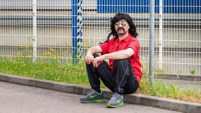 Hüsnü sitz am Strassenrand vor einem Gitterzaun