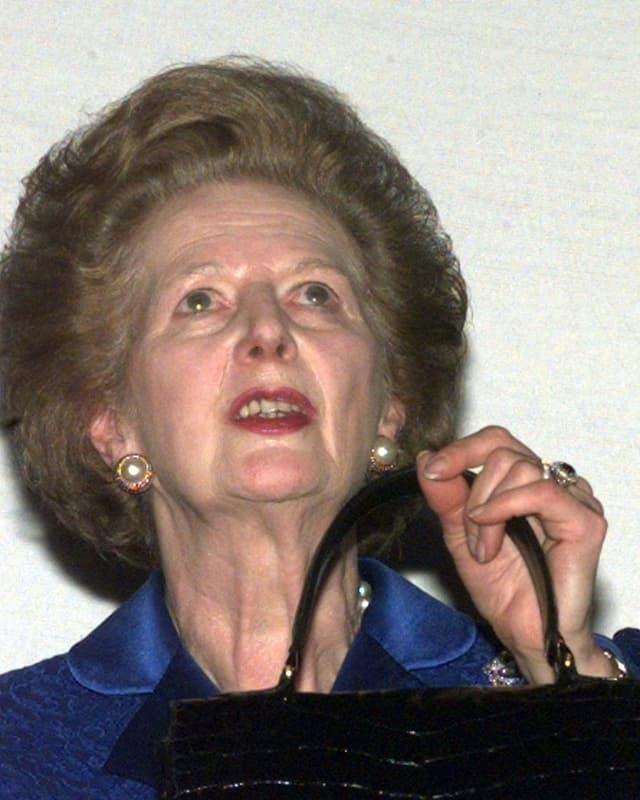 Margaret Thatcher hält ihre Handtasche und schaut gen Himmel.