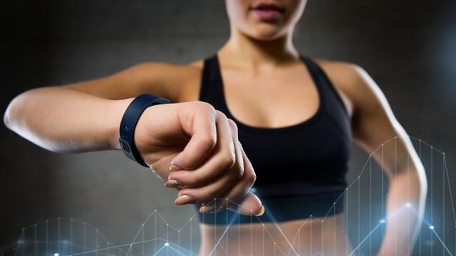 Sportlerin mit Fitnesstracker am Handgelenk.