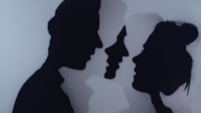 Silhouetten von einem Mann und einer Frau, die sich zu küssen gedenken.