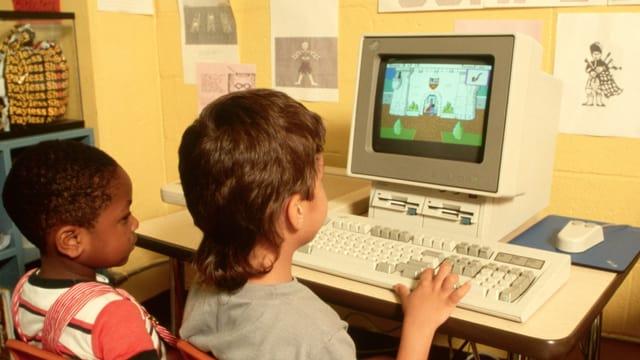 Bild von ca. 1990: Zwei Kinder sitzen vor einem altmodischen Computer, auf dem ein Spiel läuft
