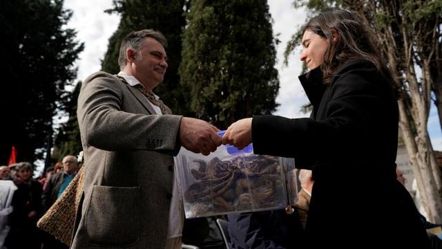 Mann übergibt einer Frau eine Plastik-Box mit menschlichen Knochen
