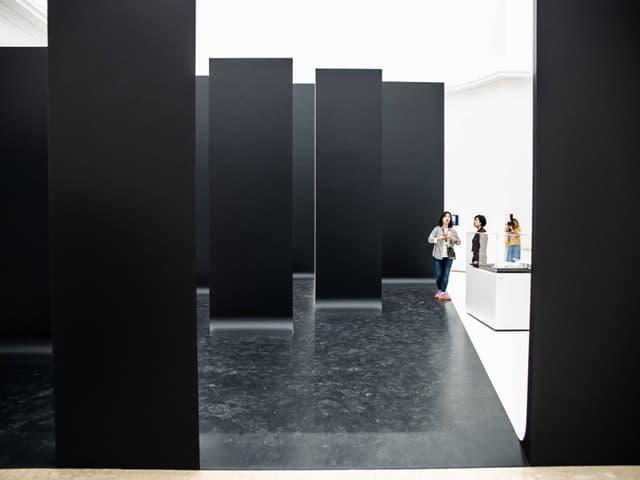 Besucher zwischen den schwarzen Mauer-Teilen