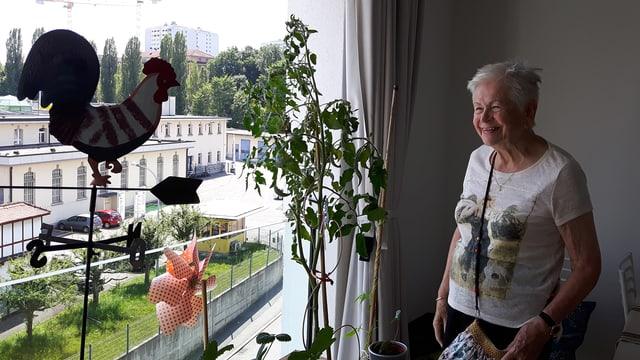 Eine ältere lachende Frau steht in einem grossen Wohnzimmer und blickt aus dem Fenster.