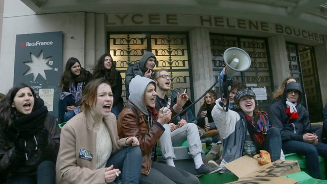 Junge Menschen sitzen auf einer Treppe und skandieren einen Sprechchor, auch ein Megafon ist zu sehen.