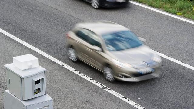 Radarkasten an Strassenseite, Auto fährt durch.