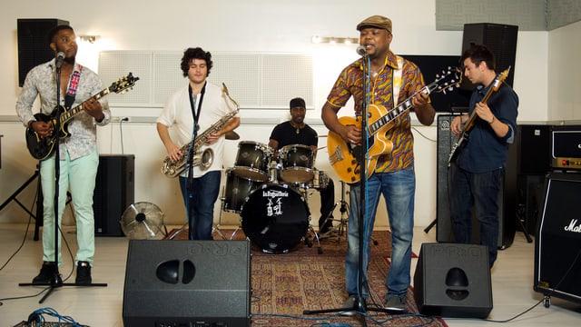 Eine fünfköpfige Band musiziert in einem kargen Raum.
