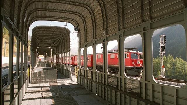 Vagun d'autos dal Vereina vid ed in tren da la Viafier retica che passa sperasvi.