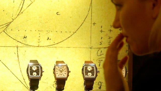 Eine Frau bestaunt drei Uhren