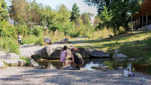 Ein Vater und seine Tochter an einem Teich im Park.