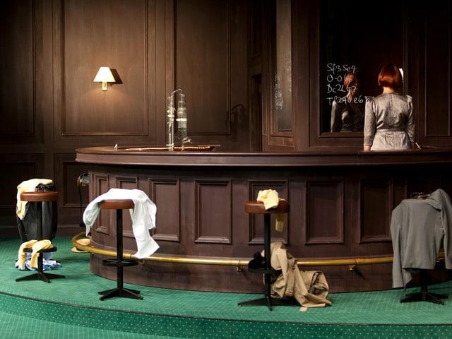 Bar in dunklem Holz, grüner Teppich, Bardame steht dahinter, auf den Barstühlen: Kleidungsstücke.