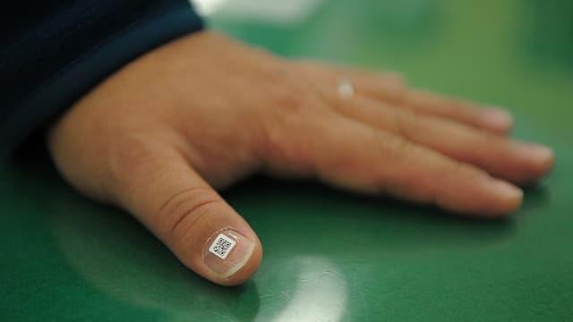 Ein QR-Code ist auf den Fingernagel eines Daumens geklebt.