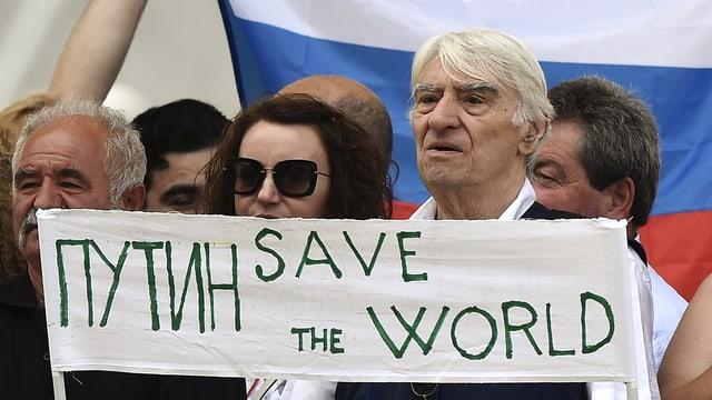 Russen vor einer grossen Landesflagge halten ein Schild hoch: «Putin rette die Welt»