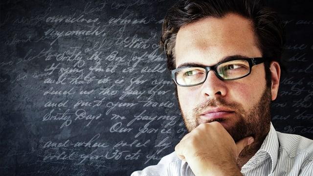 Bärtiger Mann mit Brille in Denkepose vor beschriebener Wandtafel