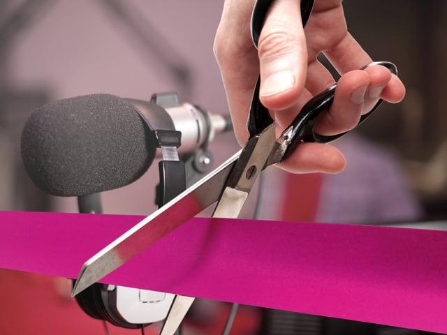 Ein purpurnes Band wird mit einer Schere durchschnitten, dahinter ein Mikrofon.